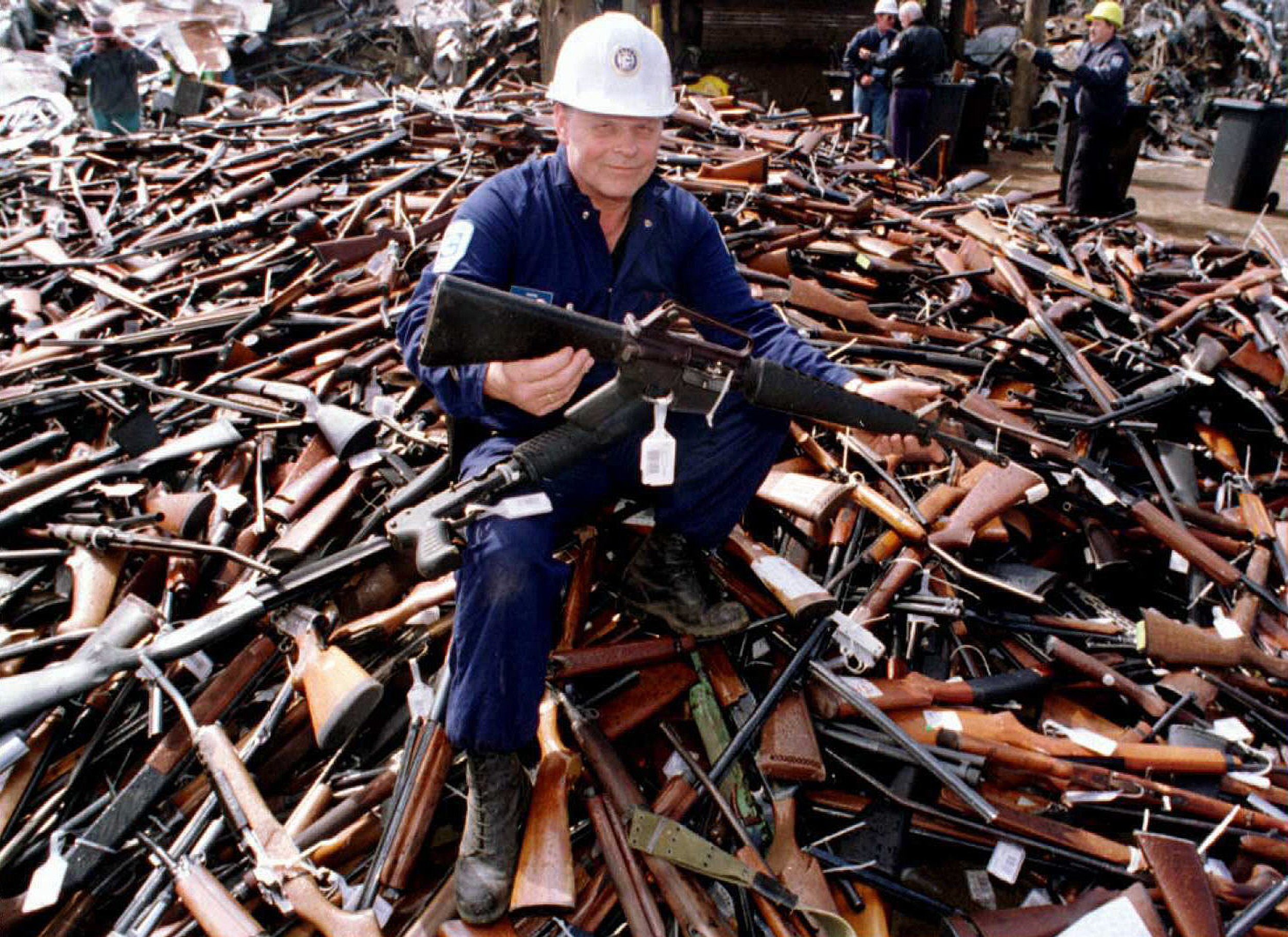 TO GO WITH US-shooting-guns-Australia,FOCUS by Martin Parryn(FILES) This file photo taken on September 8, 1996 shows Norm Legg, a project supervisor with a local security firm, holding up an armalite rifle which is similar to the one used in the Port Arthur massacre and which was handed in for scrap in Melbourne after Australia banned all automatic and semi-automatic rifles in the aftermath of the Port Arthur shooting. When Martin Bryant massacred 35 people with semi-automatic weapons at Port Arthur in 1996, then-Australian prime minister John Howard reacted swiftly by pushing for tough new national gun laws. Within a year gun licences had been tightened, a weapons buy-back was enacted and an amnesty launched for anyone holding illegal arms, moves that took more than 600,000 guns out of action. AFP PHOTO / FILES / William WEST (Photo credit should read WILLIAM WEST/AFP/Getty Images)
