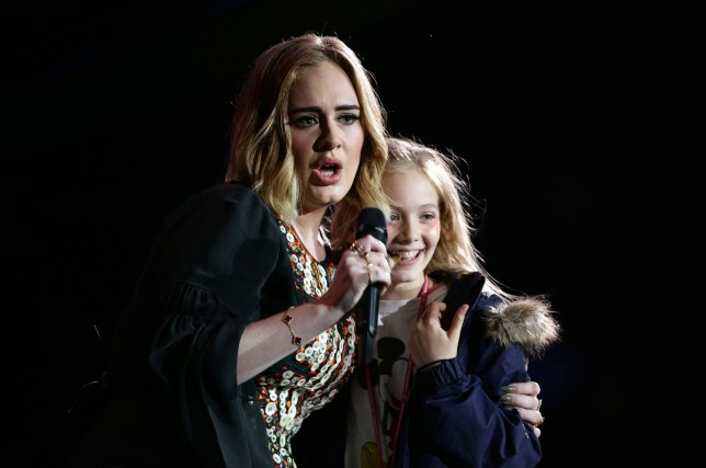 Adele on stage at the Glastonbury Festival, at Worthy Farm in Somerset with a young girl she picked out the crowd for a selfie. PRESS ASSOCIATION Photo. See PA story SHOWBIZ Glastonbury. Picture date: Saturday June 25, 2016. Photo credit should read: Yui Mok/PA Wire