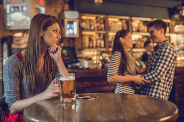 Young depressed woman sitting in the bar and holding a glass of beer while looking at happy couple laughing in the background.