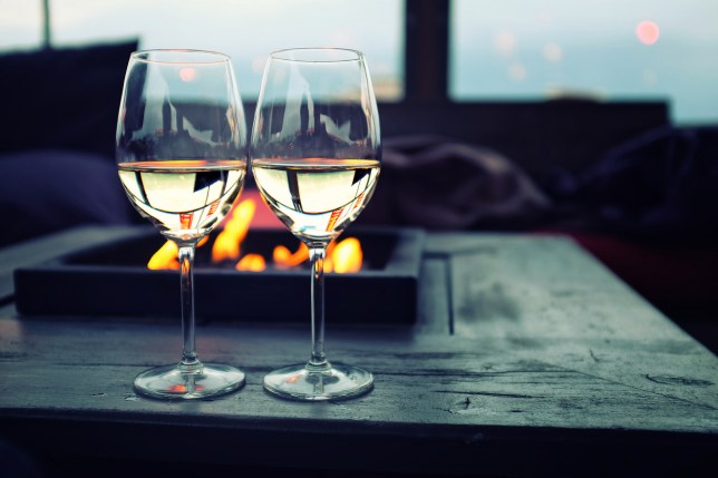 Two glasses of white wine during sunset, on a natural background with flames from a burner.