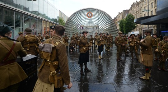People dressed as soldiers as part of a mysterious tribute to mark the centenary of the Battle of the Somme that has popped up in Glasgow. Approximately 100 people, dressed as soldiers from the Battle of the Somme, are marching through Glasgow as a preformance based tribute to those who fell. When approached they say nothing, only handing over cards showing the names of the real soldiers who died at the battle in July 1916. Each actor represents an individual soldier who fell.   JULY 01 2016,