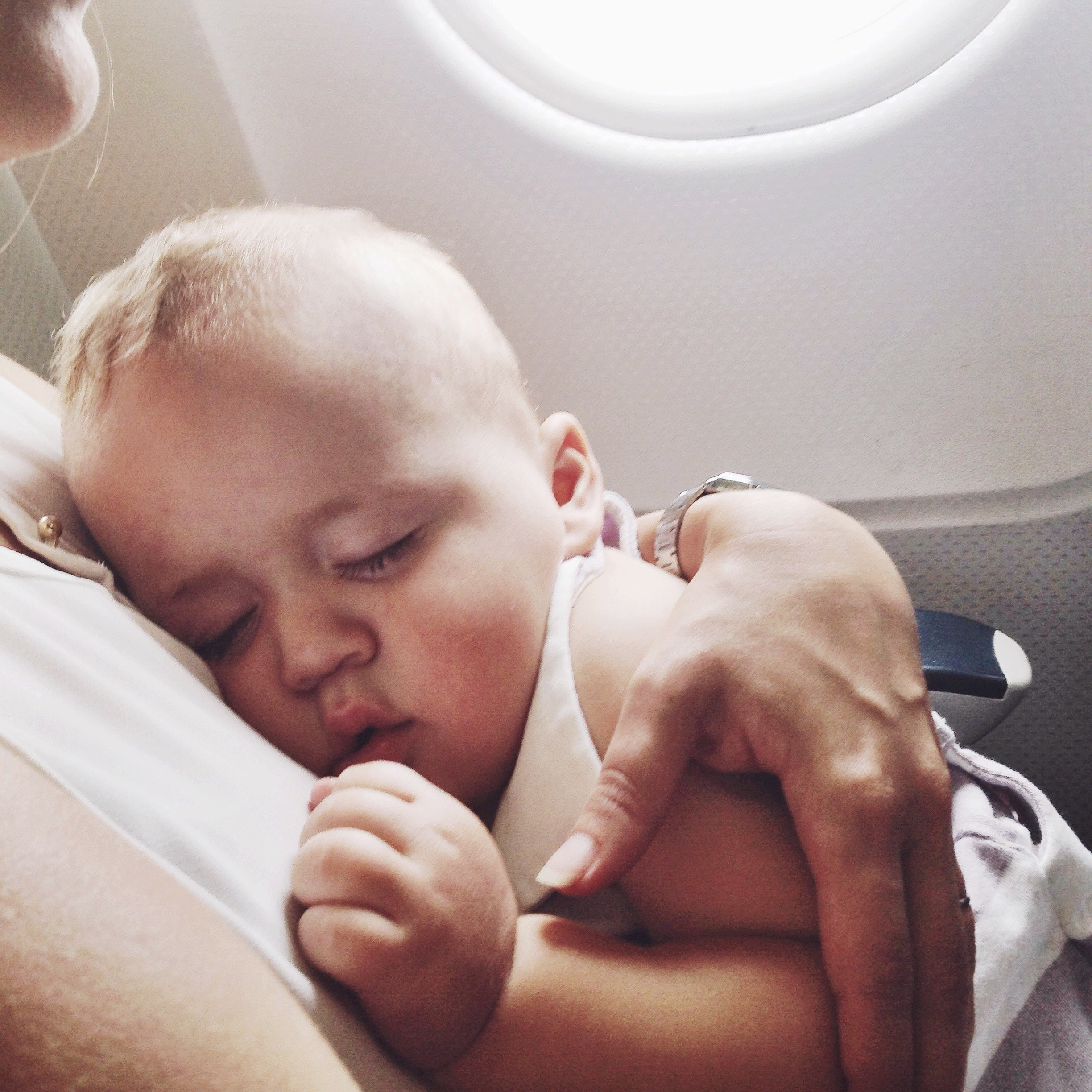 Baby boy sleeping on mother's lap in an airplane. Photo taken with an iphone5.