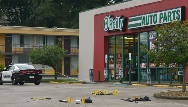 Evidence is on the ground at the crime scene at O'Reilly Auto Parts connected to the shooting on Volunteer Parkway early Thursday morning, July 7, 2016. A newspaper carrier was killed and four other people were wounded when a man opened fire on cars traveling along a parkway in East Tennessee early Thursday morning. (Andre Teague/Bristol Herald Courier via AP)