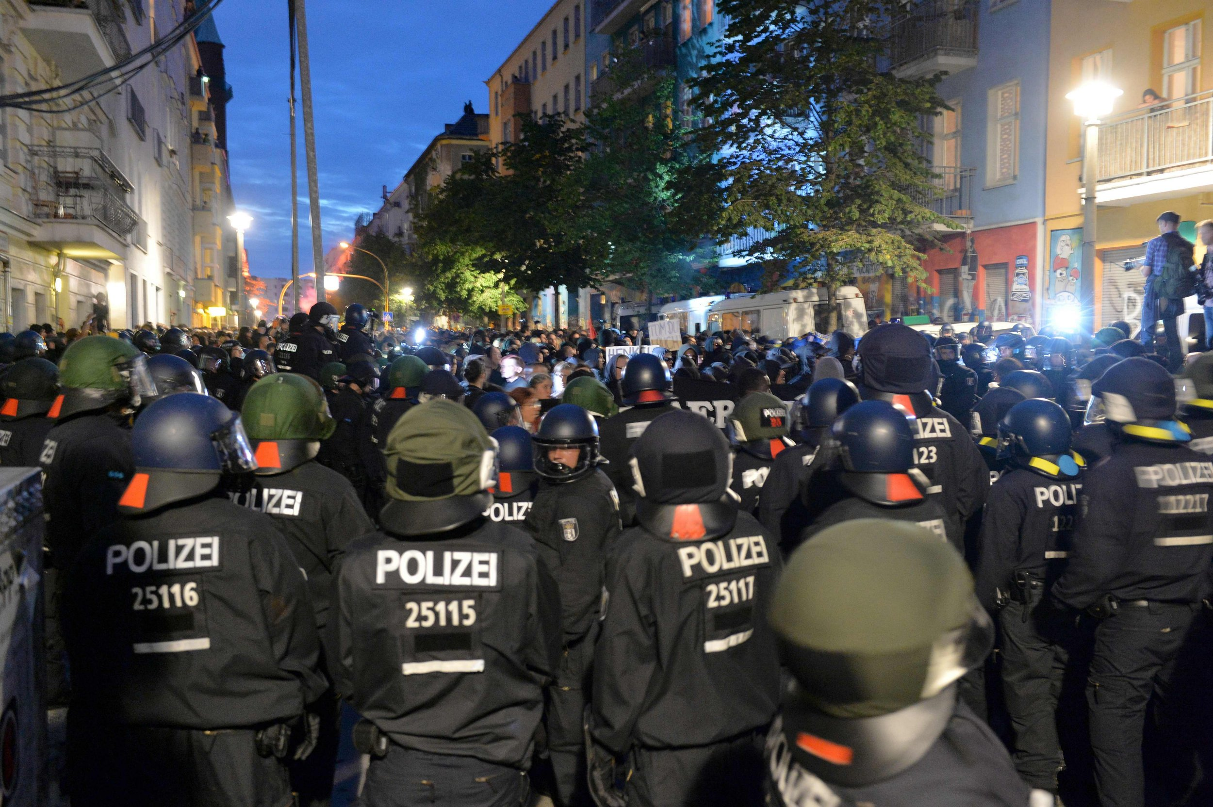 Policemen stand in front of a house in Berlin, on July 9, 2016. Police in the German capital said 123 officers were hurt in clashes with left-wing extremists who hurled rocks and bottles at them, smashed shop windows and set cars ablaze. The overnight street violence in Berlin follows weeks of escalating tensions around a building that is a centre of the far-left youth scene in the city and which has been repeatedly raided by police. / AFP PHOTO / dpa / Maurizio Gambarini / Germany OUTMAURIZIO GAMBARINI/AFP/Getty Images
