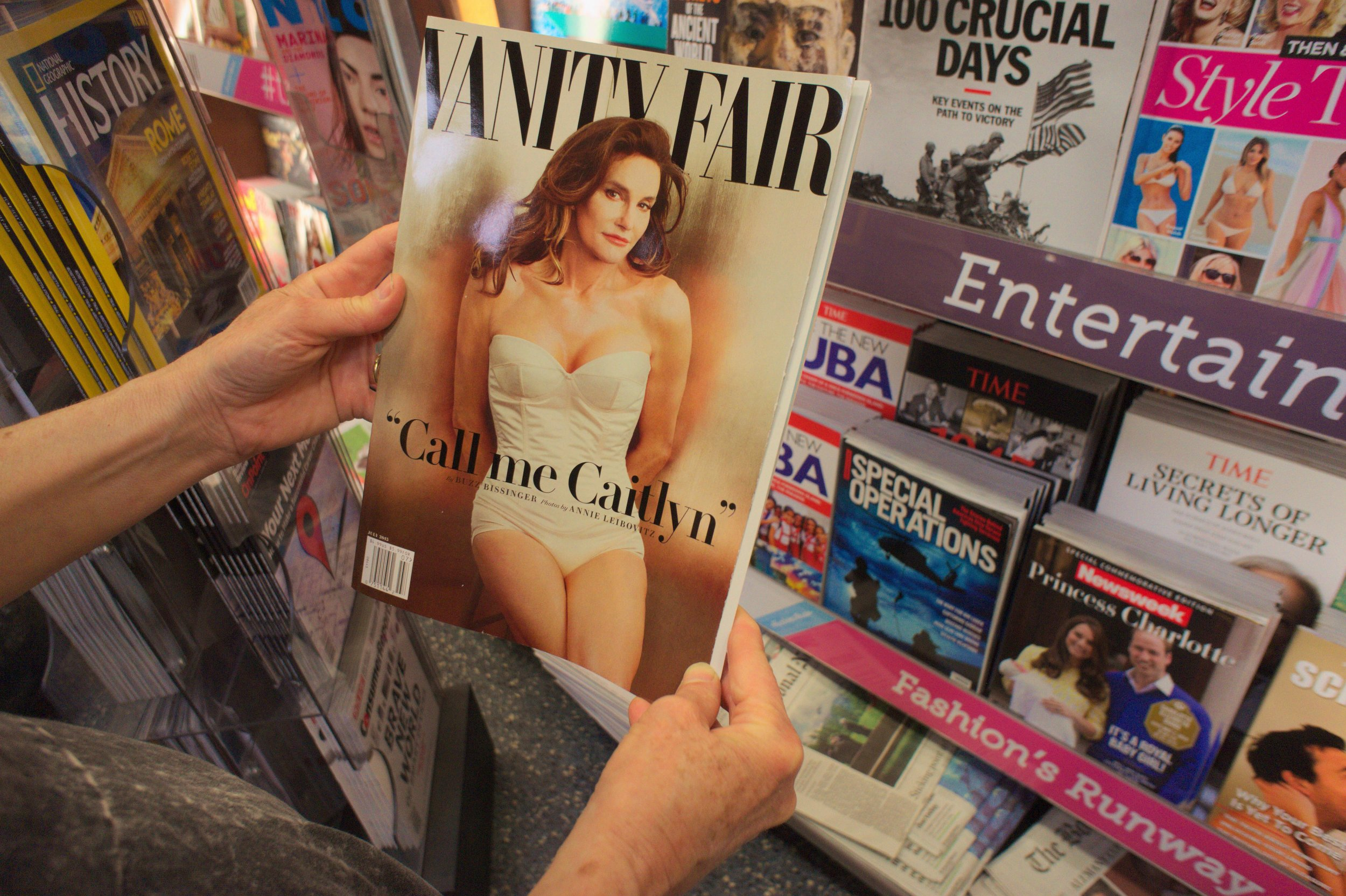 ET1G31 A reader browses a copy of the latest Vanity Fair magazine at a newsstand in New York, featuring Caitlyn Jenner, formerly Bruce Jenner on the cover and in a photo spread inside. (© Richard B. Levine)