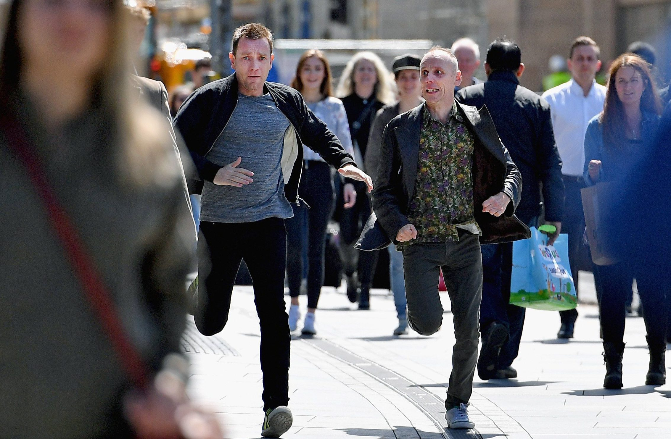 EDINBURGH, SCOTLAND - MAY 11: Actors Ewan McGregor and Ewan Bremner run on the set of the Trainspotting film sequel on Princess Street on July 13, 2016 in Edinburgh, Scotland. The long awaited Trainspotting 2 is being filmed in Edinburgh and Glasgow, 20 years after the original was released and it will also see the cast from the first film returning including Ewan McGregor, Jonny Lee Miller and Robert Carlyle. (Photo by Jeff J Mitchell/Getty Images)