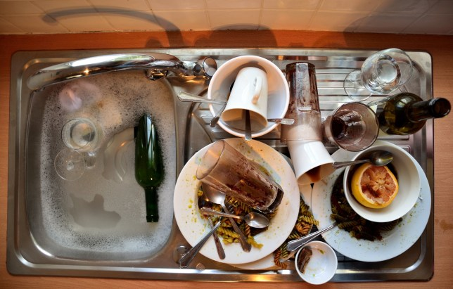Dirty plates and dishes are piled up in and next to the kitchen sink - viewed from above.
