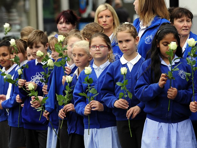 Pupils and staff of Norristhorpe Junior and Infant at School in Heckmondwike hold white roses as they watch the cortege for Labour MP Jo Cox pass in her Batley constituency in West Yorkshire, ahead of her private funeral service. PRESS ASSOCIATION Photo. Picture date: Friday July 15, 2016. The mother of two young children died on June 16 after she was attacked outside the library in Birstall, West Yorkshire. Her killing provoked a wave of shock around the UK and across the world. See PA story FUNERAL MP. Photo credit should read: John Giles/PA Wire