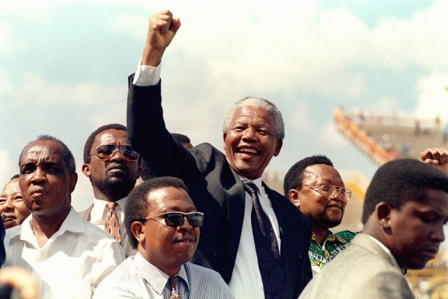 MMABATHO, SOUTH AFRICA: South African National Congress (ANC) President Nelson Mandela gives 15 March 1994 in Mmabatho a clenched fist to supporters upon his arrival for his first election rally for 27 April general elections. (Photo credit should read WALTER DHLADHLA/AFP/Getty Images)