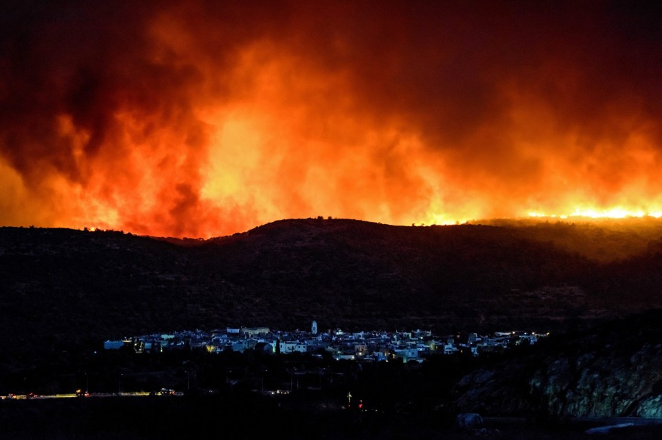 epa05441496 A picture made available on 26 July 2016 shows dense smoke over Lithi village during a wildfire on Chios island, Greece, 25 July 2016. The huge wildfire that broke out early 25 July 2016, on the island of Chios which has burned 3,500 hectares of forest and farm land, set under control. Over 90 percent of the mastic trees at the villages of Lithi, Elata and Vessa were destroyed while a large number of mastic trees were burned at the villages of Mesta, Armolia and Pyrgi. EPA/KOSTAS KOYRGIAS