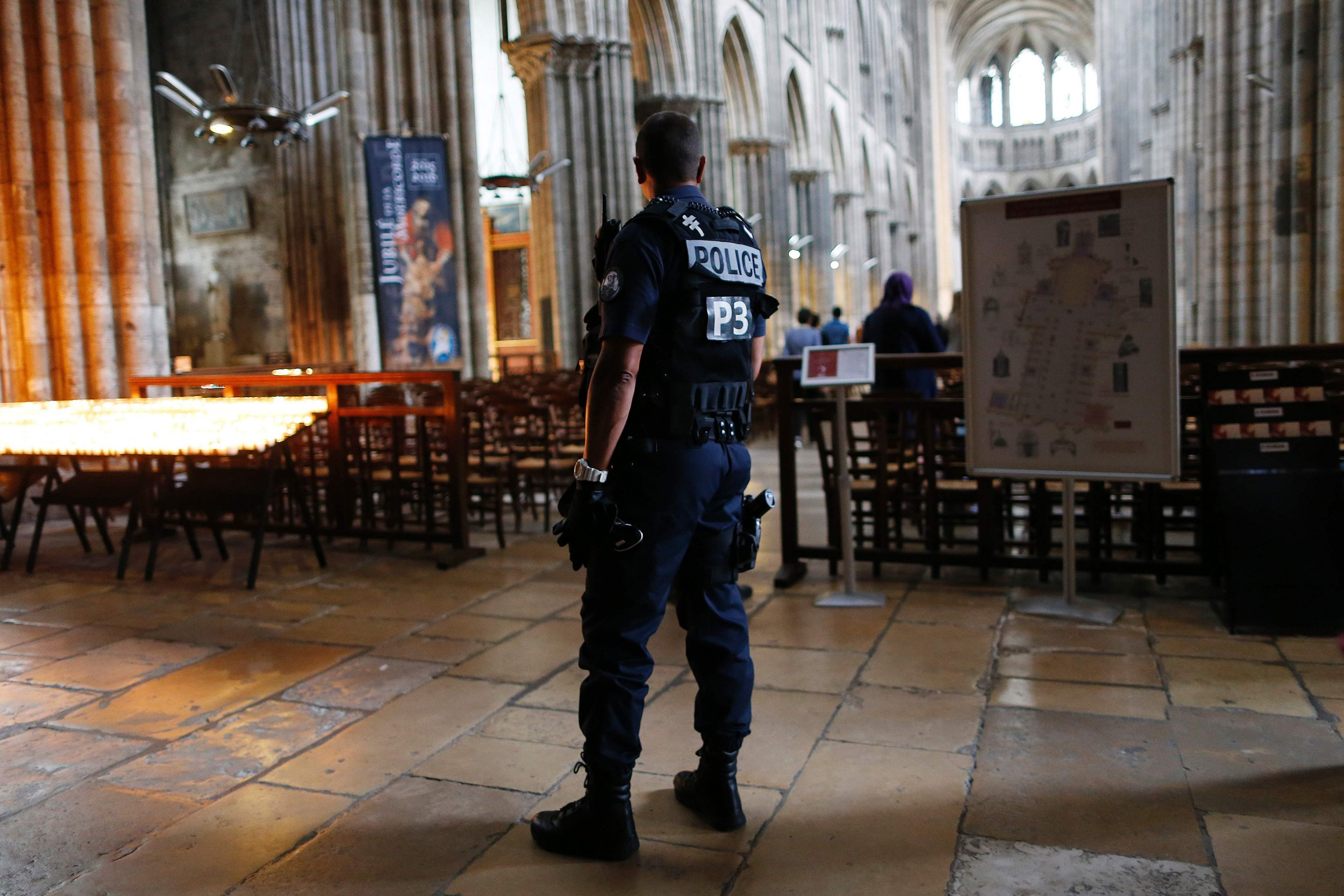 """TOPSHOT - A policeman stands guard while people arrive for a Mass at the Rouen Cathedral, on July 27, 2016 in Rouen, to pay tribute to the priest Jacques Hamel, killed on July 26 in a church of Saint-Etienne-du-Rouvray during a hostage-taking claimed by Islamic State group. France probes an attack on a church in which two men described by the Islamic State group as its """"soldiers"""" slit the throat of a priest. An elderly priest had his throat slit in a church in northern France on July 26 after two men stormed the building and took hostages. The attack in the Normandy town of Saint-Etienne-du-Rouvray came as France was still coming to terms with the Bastille Day killings in Nice claimed by the Islamic State group. / AFP PHOTO / CHARLY TRIBALLEAUCHARLY TRIBALLEAU/AFP/Getty Images"""