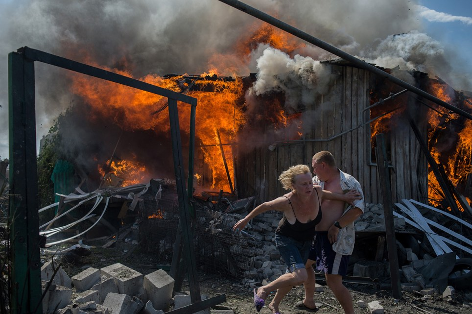 Civilians escape from a fire at a house destroyed by an air attack in Donbass, a village in Luhanskaya, eastern Ukraine, on July 2, 2014. © Valery Melnikov. Photojournalism Single Image Winner, Magnum and LensCulture Photography Awards 2016.