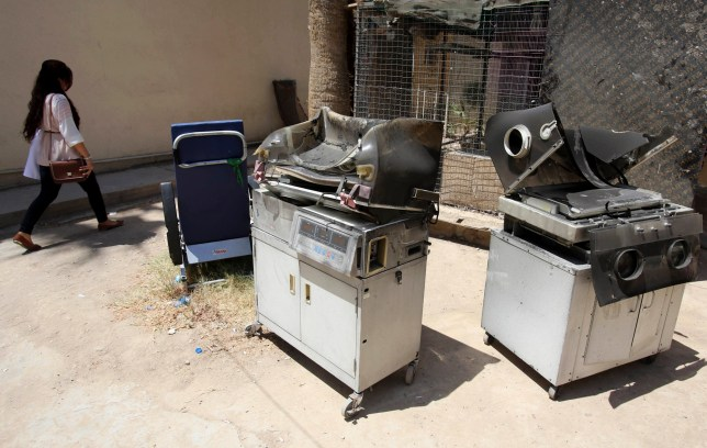 Burned incubators for newborn babies are dumped outside a maternity ward after a fire at Yarmouk hospital in western Baghdad, Iraq, Wednesday, Aug. 10, 2016. The fire ripped through the ward overnight, killing 11 newborn babies, an Iraqi spokesman said, in a deadly blaze that was likely caused by faulty electrical wiring. (AP Photo/Karim Kadim)