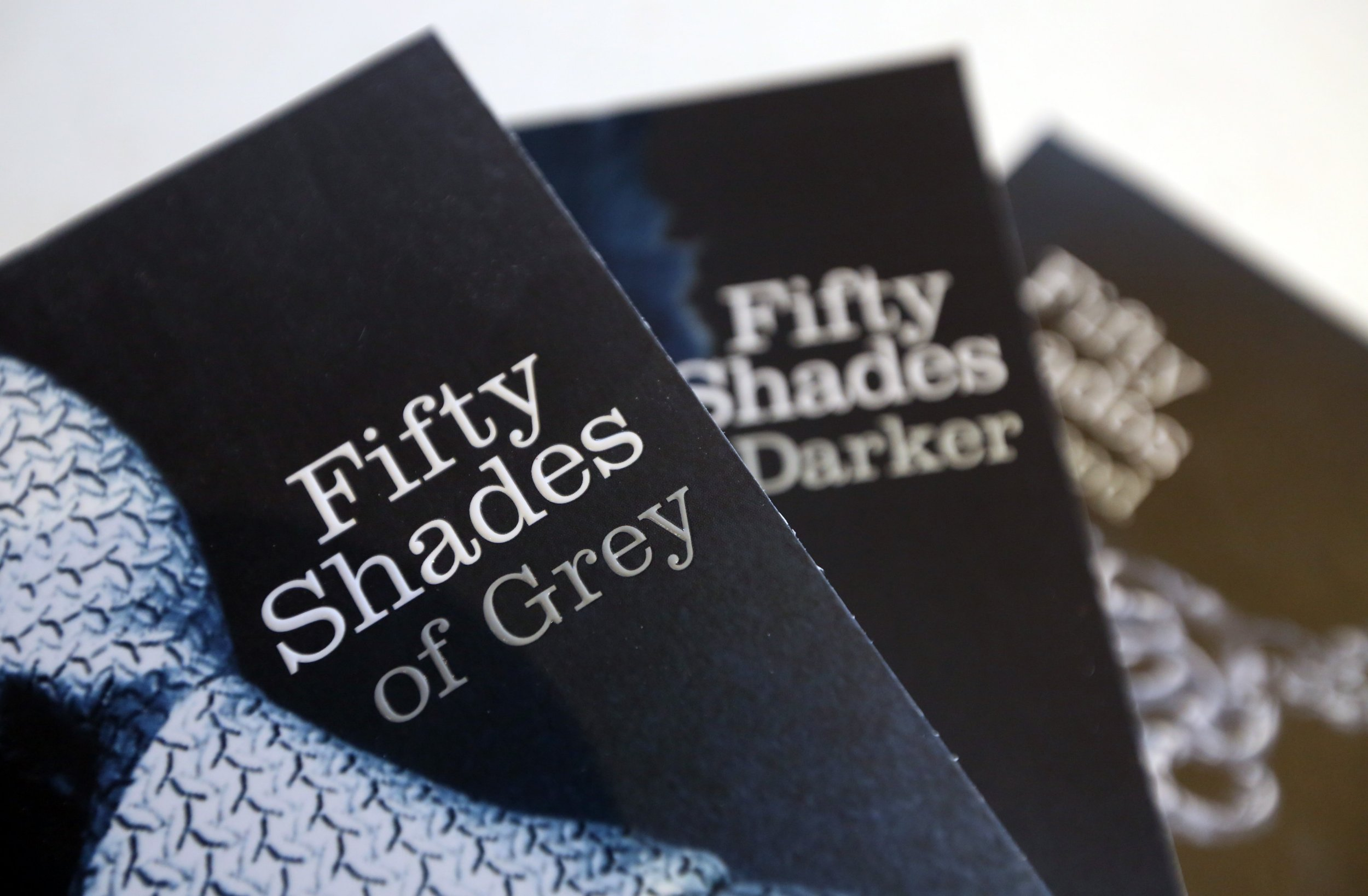 """Paperback editions of the """"Fifty Shades"""" trilogy by E.L. James, published by the Arrow, are arranged for a photograph at the U.K. headquarters of Random House in London, U.K., on Friday, April 5, 2013. Bertelsmann SE's Random House won European Union approval to buy Pearson Plc's Penguin unit to create the largest book publisher in the U.K. and the U.S. Photographer: Chris Ratcliffe/Bloomberg via Getty Images"""
