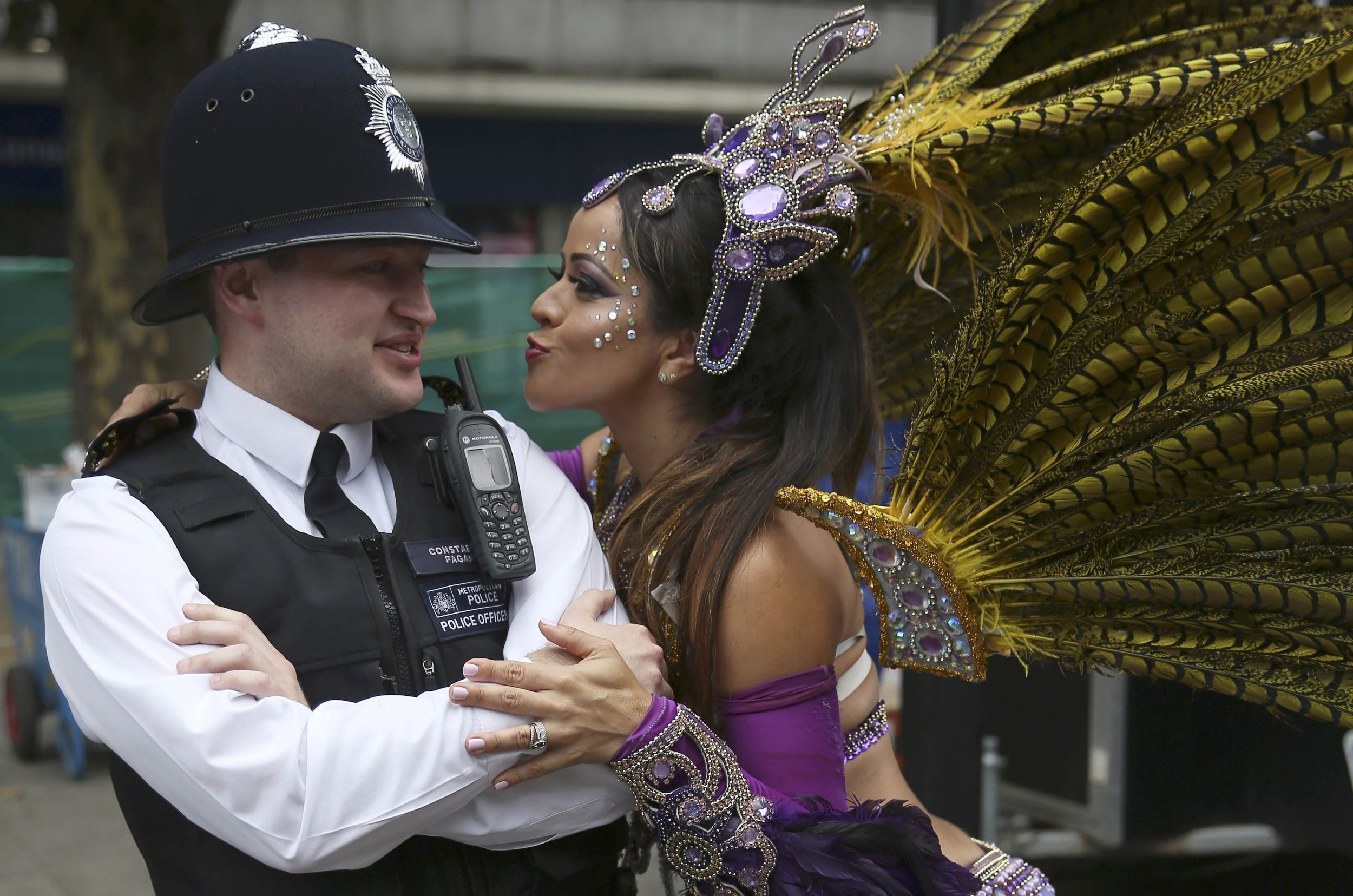 A performer dances with police during the Notting Hill Carnival in London, Britain August 29, 2016. REUTERS/Neil Hall