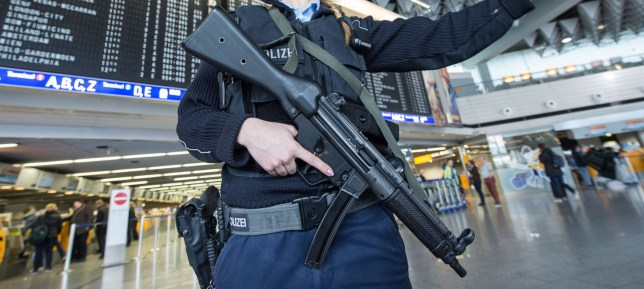 An armed policewoman gestures in Frankfurt Airport, on March 22, 2016, in Frankfurt, western Germany. The increased security comes in the wake of the explosions in Brussels, that, according to several media, have claimed more lives. / AFP / DPA / Boris Roessler / Germany OUT (Photo credit should read BORIS ROESSLER/AFP/Getty Images)