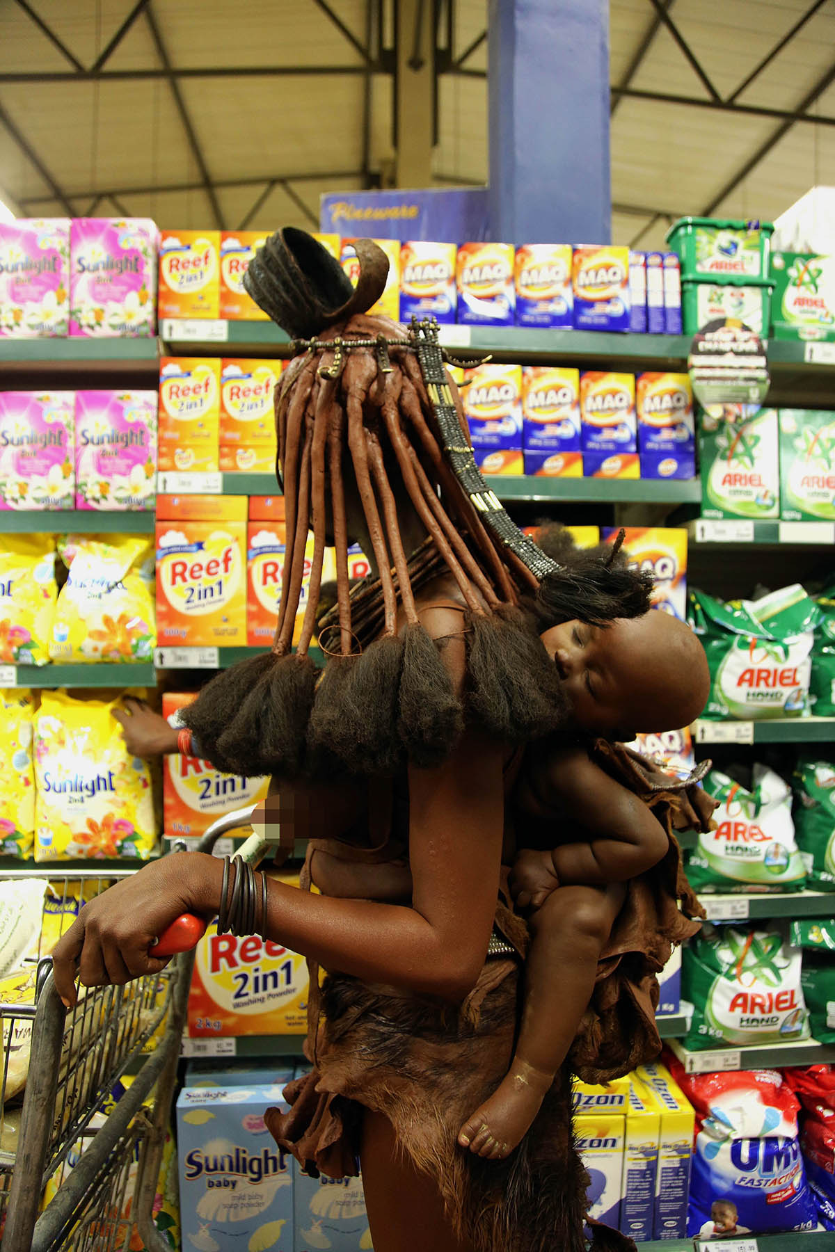 PIC BY BJORN PERSSON / CATERS NEWS - (PICTURED: A female member of the Himba Tribe and her infant in a supermarket.) - These striking images show an elegant African tribeswoman in traditional dress and mud for sunscreen - checking out deals on washing powder. The woman, from the Himba tribe in Opuwo, Namibia, popped into her local grocery store to pick up a few of lifes essentials.Himba tribespeople lead a very traditional lifestyle, and so the photos reveal the very pervasive nature of globalisation. The lady, thought to be in her early twenties, was pictured by Swedish wildlife and documentary photographer Bjorn Persson. SEE CATERS COPY.