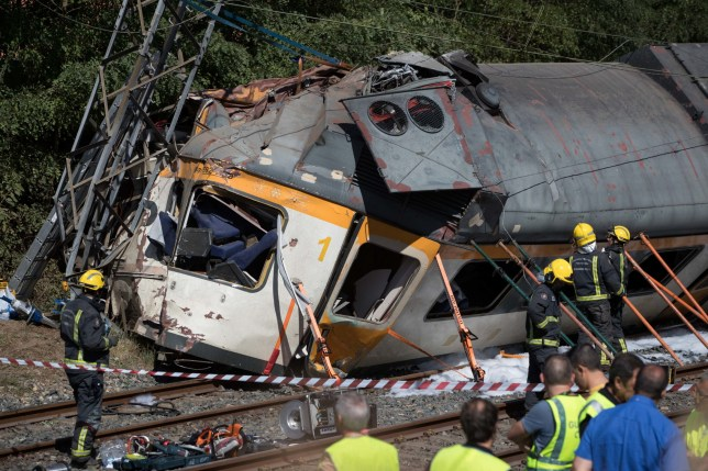Emergency personnel attend the scene after a passenger train traveling from Vigo to Porto, in neighboring Portugal, derailed in O Porrino, in Spain's northwestern Galicia region, killing and injuring people, authorities said Friday Sept. 9, 2016 . The train had three cars. The front one came completely off the track and hit a post next to the line, leaving it leaning to one side. The back two cars were partly off the tracks. Spanish media said the train was carrying around 60 passengers.(AP Photo/Lalo R. Villar)