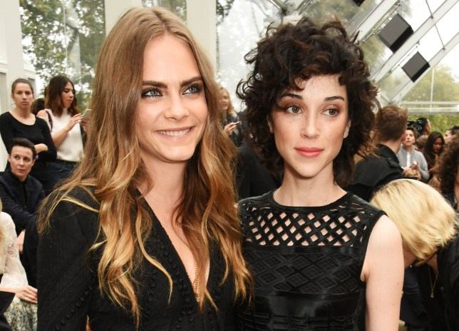 LONDON, ENGLAND - SEPTEMBER 21: Cara Delevingne (L) and Annie Clark attend the Burberry Womenswear Spring/Summer 2016 show during London Fashion Week at Kensington Gardens on September 21, 2015 in London, England. (Photo by David M. Benett/Dave Benett/Getty Images for Burberry)