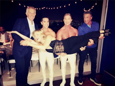 Tony Blair pictured with Sylvester Stallone and two acrobats carrying Kate Hudson
