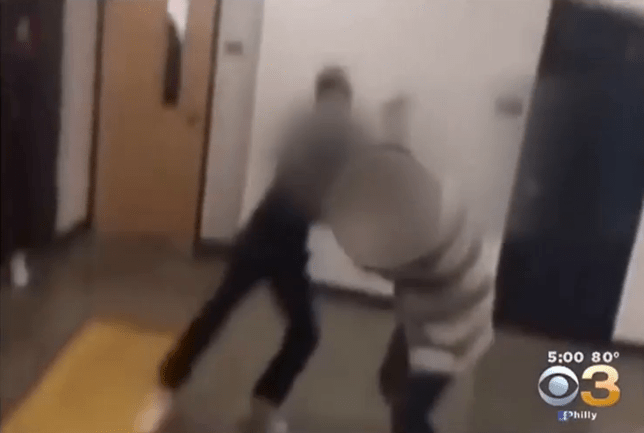 Teacher 'physically fighting' with a student in school corridor because he was late to class Credit: CBS