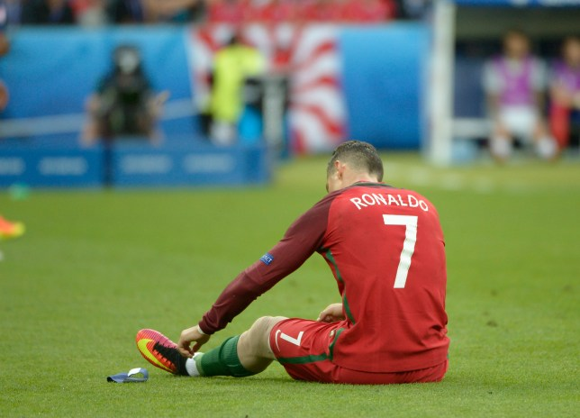 PARIS, FRANCE - JULY 10: Cristiano Ronaldo of Portugal sits on the pitch after being injured during the UEFA EURO 2016 Final match between Portugal and France at Stade de France on July 10, 2016 in Paris, France. Portugal won the match 1-0. (Photo by Bob Thomas/Popperfoto/Getty Images).