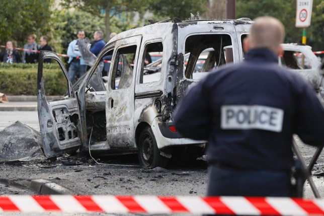 """A police officer stands guard near a burned police vehicle (back) and a van in Viry-Chatillon on October 8, 2016 after police in their patrol car were attacked by individuals who launched Molotov cocktails, leaving two officers injured. Two officers were """"seriously injured"""" when ten individuals launched Molotov cocktails at their vehicle, according to a police source. The officers in their vehicle were responsible for monitoring footage from a camera near a traffic light in Viry-Chatillon. / AFP PHOTO / Thomas SAMSONTHOMAS SAMSON/AFP/Getty Images"""