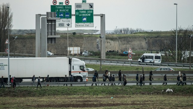 """Migrants and refugees walk on the A16 near the Eurotunnel site on December 3, 2015 in Coquelles.nFrance's prisons watchdog condemned the government on December 2 for locking up migrants in a bid to clear the notorious camp known as """"the Jungle"""" near Calais. In a strongly-worded statement to the government, the head of the official CGLPL jails watchdog Adeline Hazan said authorities must stop """"abusing"""" rules on migrant detention, saying there had been """"serious breaches of fundamental rights"""". nn / AFP / PHILIPPE HUGUEN (Photo credit should read PHILIPPE HUGUEN/AFP/Getty Images)"""