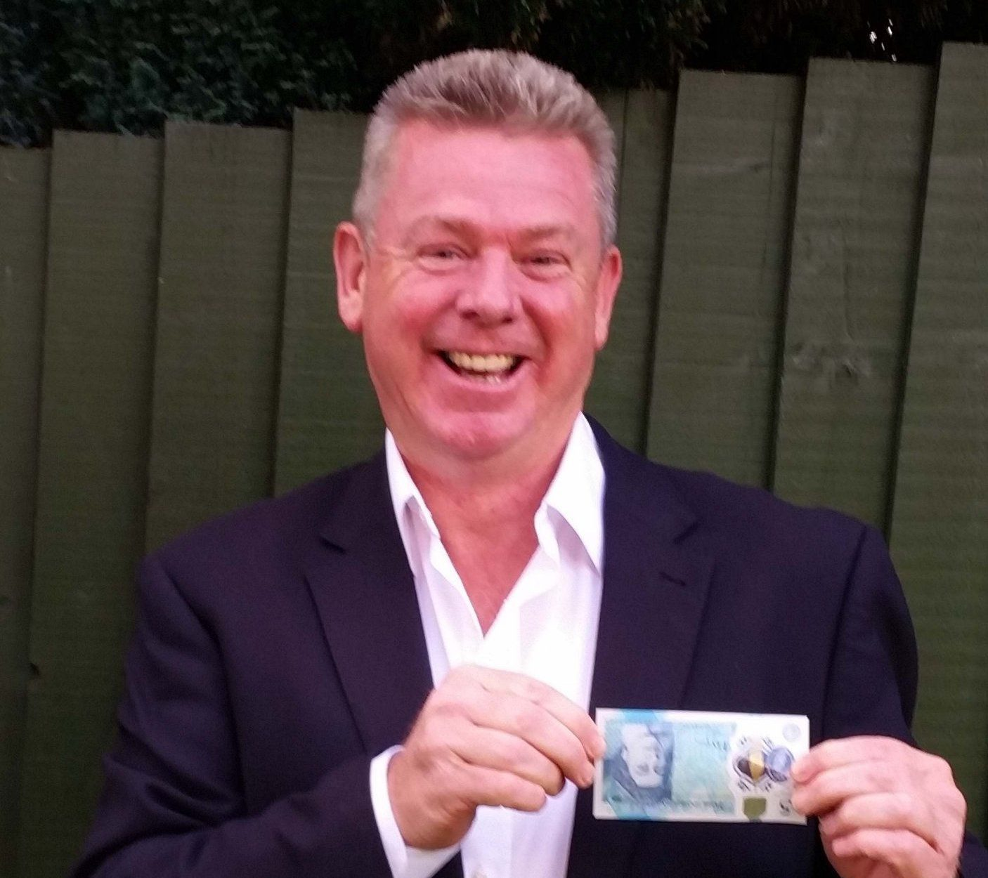PIC FROM MERCURY PRESS (PICTURED: MIKE HARRIS, 54, WITH THE 'UPSIDE DOWN' FIVE POUND NOTE HE LISTED ON EBAY) A prankster who was perplexed by collectors paying thousands for new £5 notes listed one on eBay as ëa rare UPSIDE DOWN noteí ñ sparking a bidding war on the item that hit almost £66,000. Ex-Navy man Mike Harris, 54, said he had watched the new £5 notes hit ësilly pricesí as collectors scrabbled to get hold of unique bar codes. So Mike took a picture of a £5 he turned upside down and listed it on the popular auction site as a joke but was left stunned when the bids started pouring in and hit £65,551 with 68 bids. His listing claimed to be verified for its authenticity by the Department of Upside-down Printed English Denominations (DUPED). SEE MERCURY COPY