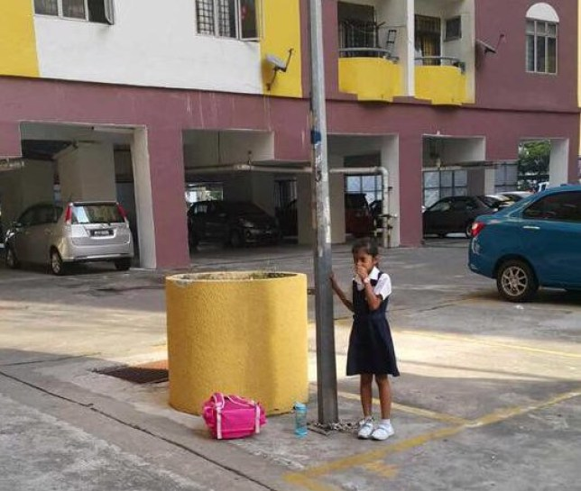 This is the shocking moment a eight-year-old girl is chained to a pole by her mother - after she refused to go to school. See SWNS story SWCHAIN; Horrified onlookers heard the girl crying while sucking her thumb in the car park outside the family's apartment on Wednesday afternoon. They tried to free her but the thick chain had been secured with two padlocks - leaving the youngster stuck for over an hour before police arrived. She told cops that her 30-year-old mum had become angry and punished her after she said did not go to mandarin classes at school in Kuala Lumpur, Malaysia.