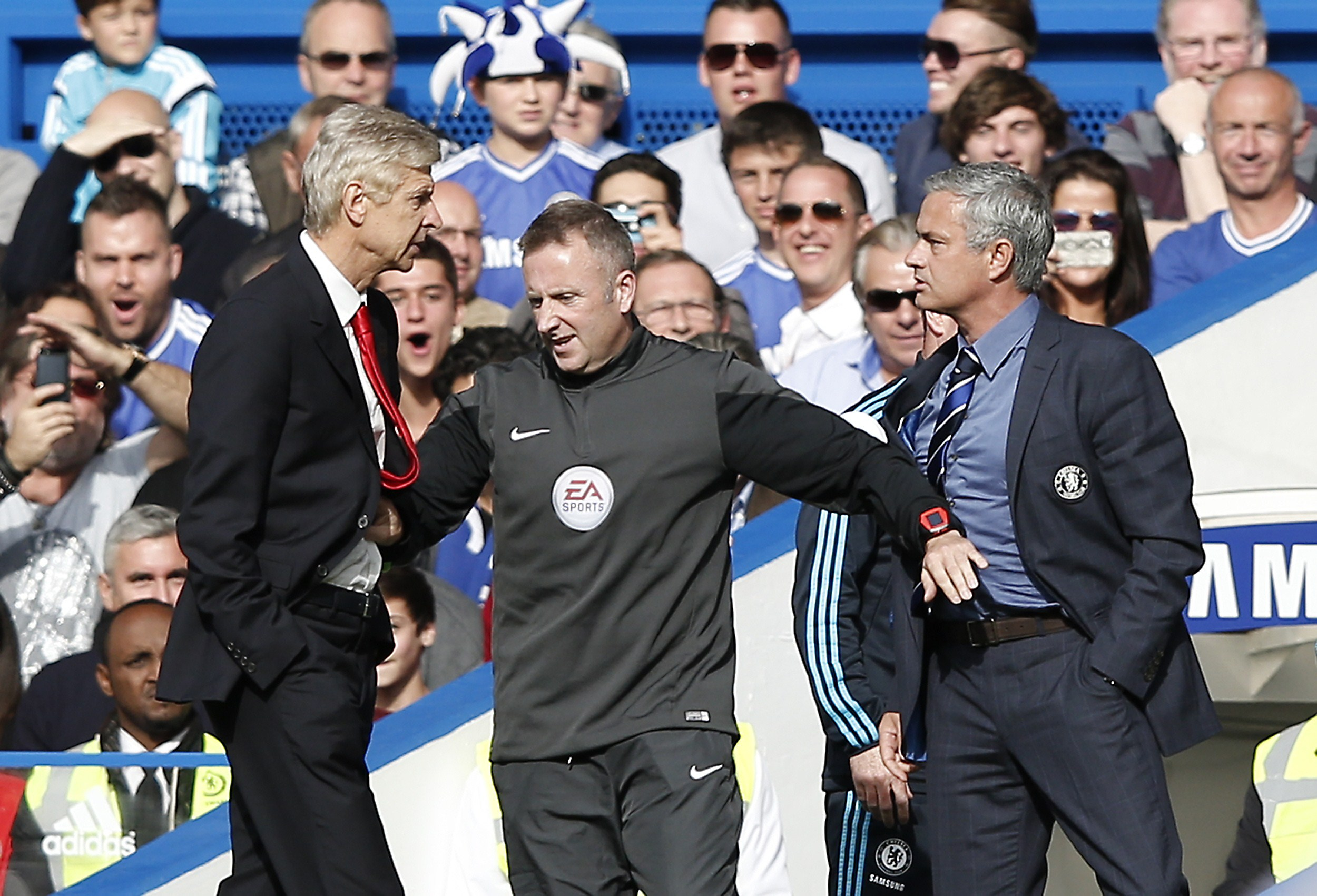 """Chelsea's Portuguese manager Jose Mourinho (R) and Arsenal's French manager Arsene Wenger (L) are kept apart by the fourth official Jonathan Moss during the English Premier League football match between Chelsea and Arsenal at Stamford Bridge in London on October 5, 2014. AFP PHOTO/ADRIAN DENNIS == RESTRICTED TO EDITORIAL USE. NO USE WITH UNAUTHORIZED AUDIO, VIDEO, DATA, FIXTURE LISTS, CLUB/LEAGUE LOGOS OR """"LIVE"""" SERVICES. ONLINE IN-MATCH USE LIMITED TO 45 IMAGES, NO VIDEO EMULATION. NO USE IN BETTING, GAMES OR SINGLE CLUB/LEAGUE/PLAYER PUBLICATIONS. == (Photo credit should read ADRIAN DENNIS/AFP/Getty Images)"""