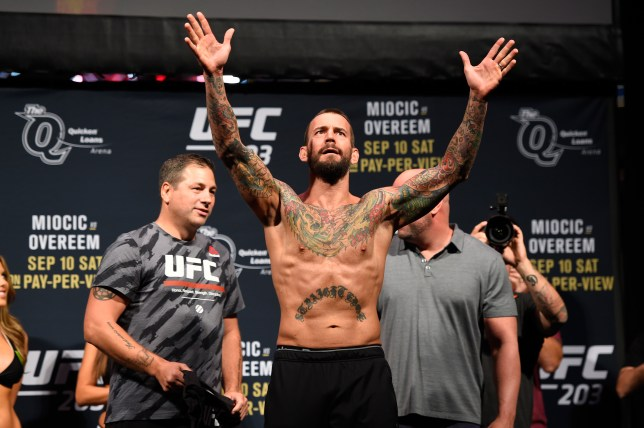 CM Punk poses on the scales