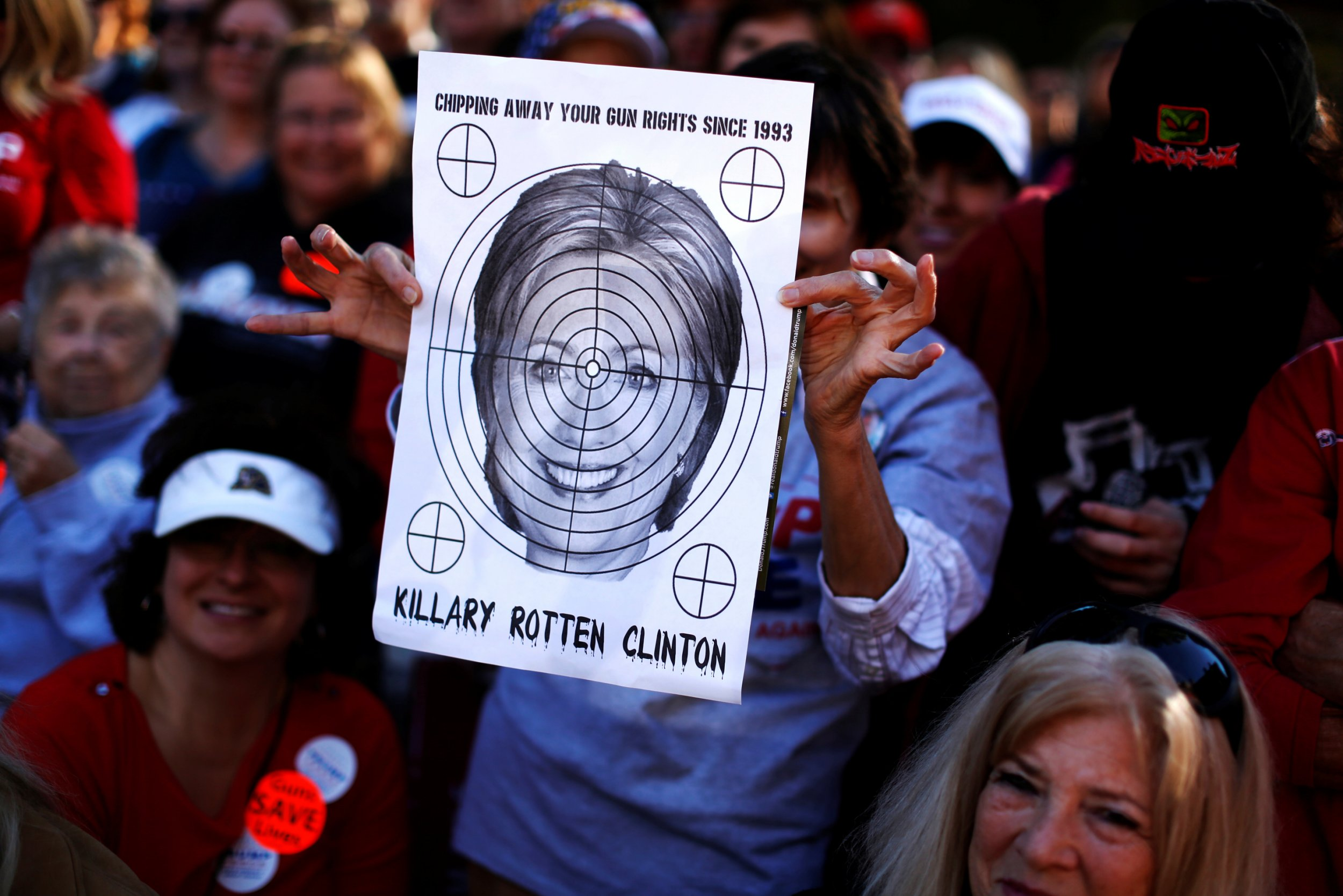 A supporter of Republican U.S. presidential nominee Donald Trump holds a shooting target with image of Hillary Clinton at a campaign rally in Virginia Beach, Virginia, U.S. October 22, 2016. REUTERS/Jonathan Ernst - RTX2Q0YZ