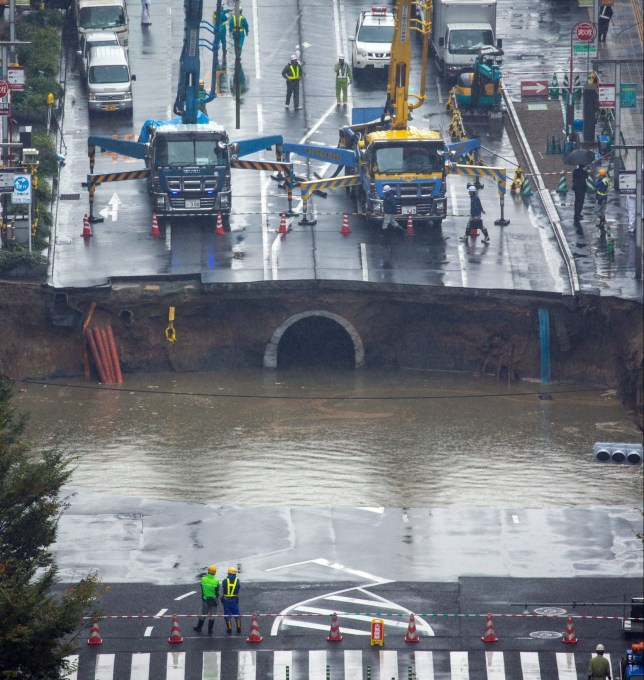 epa05621786 A large sinkhole cuts off an avenue in central Fukuoka, southwestern Japan, 08 November 2016. According to local media reports, the sinkhole has caused blackouts and disrupted traffic. Authorities have evacuated surrounding buildings in case of further damage. There were no immediate reports of damage or injuries. EPA/HIROSHI YAMAMURA