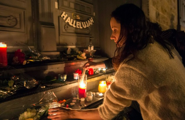 "A woman places a candle in front of the home of legendary singer and poet Leonard Cohen Thursday, Nov. 10, 2016 in Montreal. Cohen, the baritone-voiced Canadian singer-songwriter who seamlessly blended spirituality and sexuality in songs like ""Hallelujah,"" ''Suzanne"" and ""Bird on a Wire,"" has died at age 82, his son said Thursday. (Paul Chiasson/The Canadian Press via AP)"
