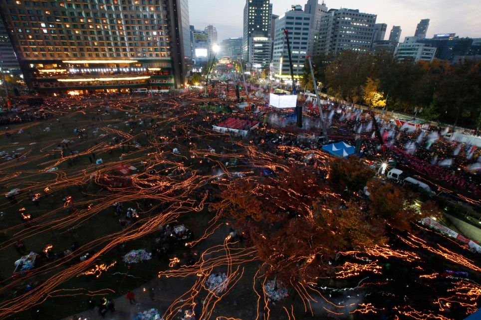 In this photo taken with a long exposure, South Koreans march toward the presidential house with candlelight during a protest against South Korean President Park Geun-hye on a main street in Seoul Friday, Nov. 12, 2016. Tens, and possibly hundreds, of thousands of South Koreans marched in Seoul on Saturday demanding the ouster of Park in one of the biggest protests in the country since its democratization about 30 years ago. (Jeon Heon-kyun/Pool Photo via AP)