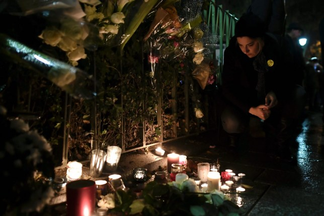 A woman kneels around flowers and candles laid next to the Bataclan concert hall in Paris on November 12, 2016, a few hours before the reopening concert by British musician Sting to mark the first anniversary of the November 13 Paris attacks. Rock star Sting reopens the Bataclan on November 12, the revered Paris concert hall where jihadists massacred 90 people, with a hugely symbolic show to mark the first anniversary of France's bloodiest terror attacks. Scores of survivors of the Bataclan assault -- the worst of the gun and suicide attacks across the city that night which left 130 dead -- will attend the concert, the dominant event in a weekend of otherwise low-key commemorations. / AFP PHOTO / PHILIPPE LOPEZPHILIPPE LOPEZ/AFP/Getty Images