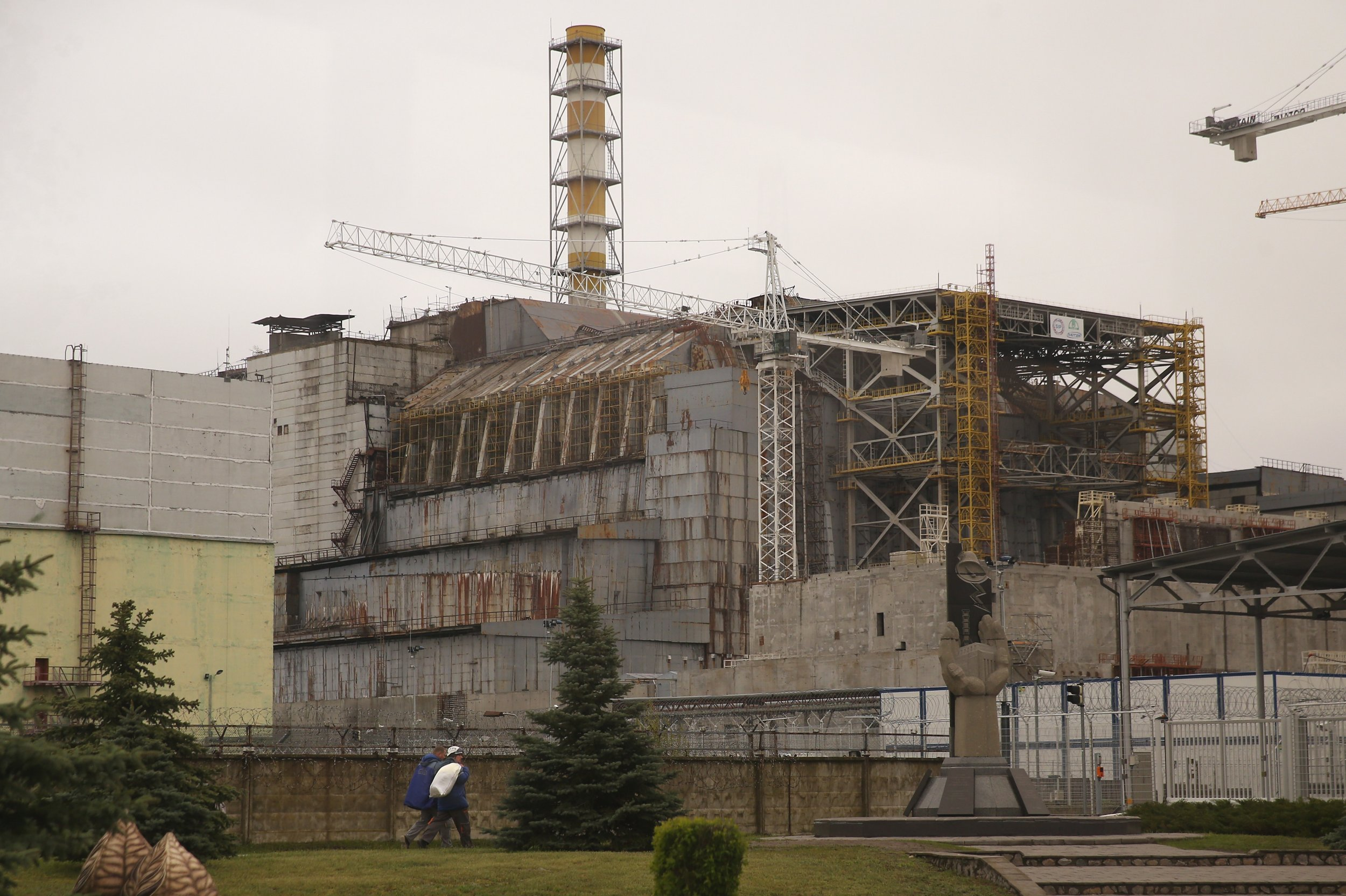 CHORNOBYL, UKRAINE - APRIL 26:  In this photograph taken through a bus window workers walk near the sarcophagus that encloses stricken reactor number four at the Chernobyl nuclear power plant on the 30th anniversary of the Chernobyl nuclear accident on April 26, 2016 near Chornobyl, Ukraine. On April 26, 1986 workers at the Chernobyl nuclear power plant inadvertantly caused a meltdown in reactor number four, causing it to explode and send a toxic cocktail of radioactive fallout into the atmosphere in the world's worst civilian nuclear incident. The fallout spread in plumes across the globe, covering much of Europe and reaching as far as Japan. Today large swathes in Ukraine and Belarus remain too contaminated for human habitation and strong evidence points to ongoing adverse health impacts for people in the larger region.  (Photo by Sean Gallup/Getty Images)