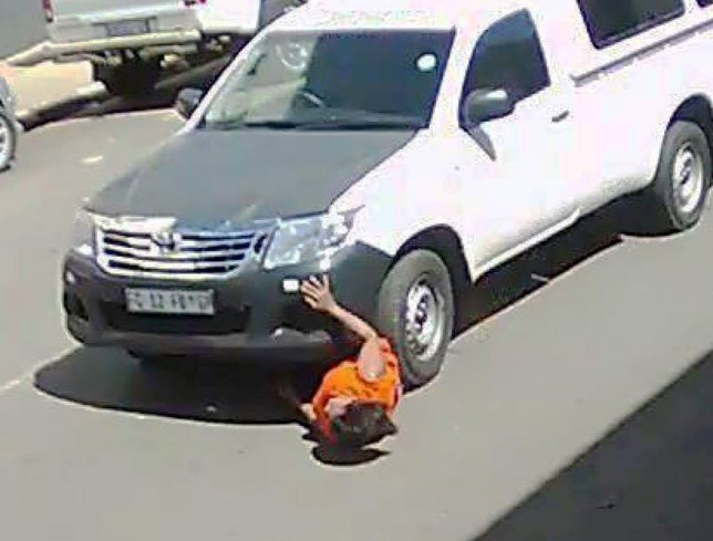 """Pic shows: The moment of the hit. A woman has astonished medics by surviving a brutal hit and run crash where she was dragged for 60ft under the front wheels of a pick-up truck. CCTV footage of the horrific crash has become a grim online hit, now viewed by tens of thousands of social media users after it was shared online. The footage - captured in Johannesburg, South Africa - shows the victim knocked over and pushed in front of the truck as she is crossing the road at a corner crossing. After taking the corner at high speed, the woman was left instantly sandwiched between the front wheel and the bodywork. She was then dragged down the street for at least 60 feet with her head and shoulders sticking out of the wheel arch. The footage ends before it shows what happened when the truck stopped, but local media reports that the driver fled after the woman fell free. Astonishingly, she is reported to have survived and is recovering at Charlotte Maxeke Johannesburg Academic Hospital. Police are understood to be waiting for an official medical report of the hit and run injuries before they open a formal inquiry. But South Africa's Crime Intelligence and Community Awareness has already started a nationwide search on its Facebook page for the driver. Under a terrifying close up picture of the victim being dragged along by the white truck they say: """"Please share to all groups and pages - Let's help find the perp from the horrific hit and run incident."""" And on YouTube furious watchers have condemned the driver. One - named as 'FrozenEternity' said: """"I bet he was on his phone. How did he not see those people!!!ø"""" Another called 'Gavin VON MEYER' added: """"Oh My Lord. I hope the woman is going to recover. And hope that pig driver gets caught.ø"""" A third identified as 'Ephraim Galetta' said: """"I hope that pig has sleepless nights.ø"""" (ends)"""