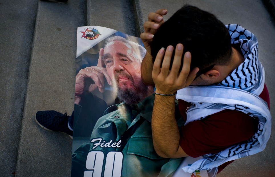 Palestinian medical student Adham Motawi, with an image of Fidel Castro, holds his head in disbelief during a gathering in Castro's honor in Havana, Cuba, Saturday, Nov. 26, 2016, the day after his death. Cuba will observe nine days of mourning for the former president who ruled Cuba for half a century. (AP Photo/Ramon Espinosa)