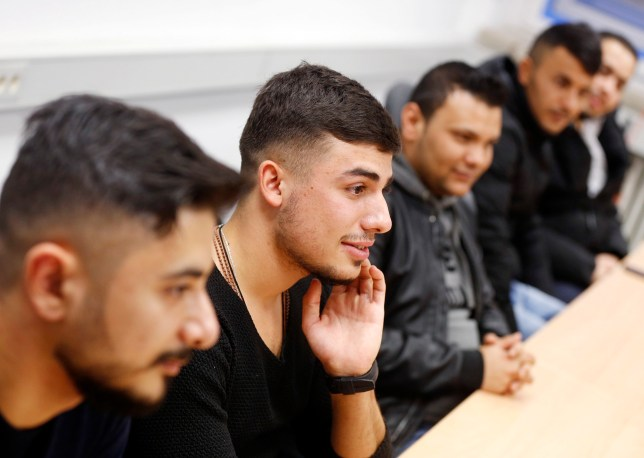 In this Nov. 22, 2016 photo Essam Kadib al Ban, second from left, takes part in a flirt workshop for refugees in Dortmund, Germany. Horst Wenzel, who usually teaches German men how to approach women, volunteers his skills to help with integrating some of the more than 1 million refugees who have arrived over the past two years in Germany. (AP Photo/Michael Probst)