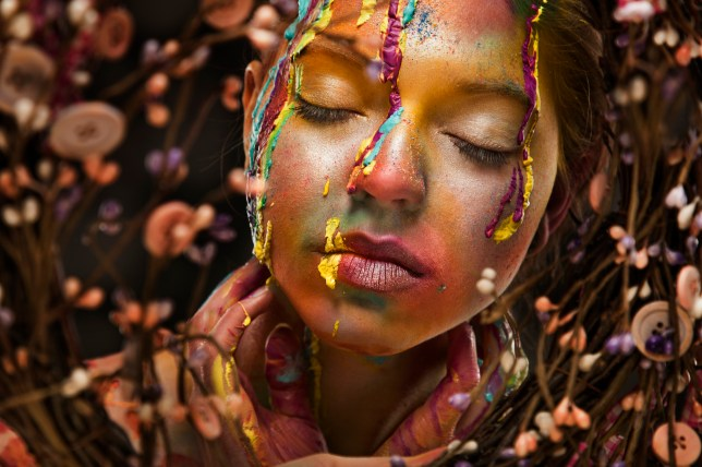 Portrait of a woman with a colorful make-up - dripping face paint and colorful shadows.
