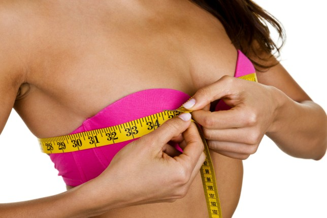 Woman wearing a pink bra and measuring her breast size