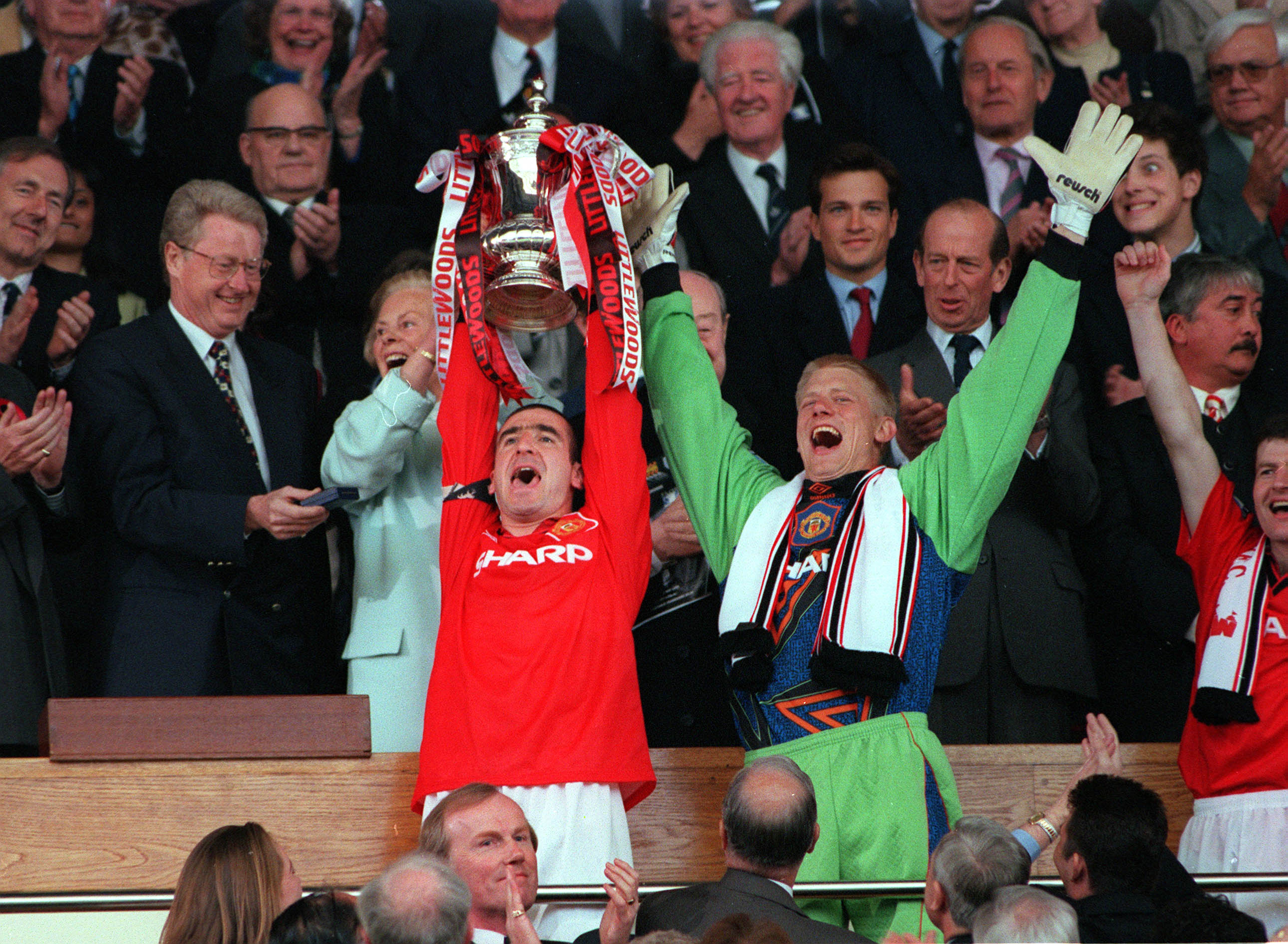 Football, 1996 FA Cup Final, Wembley, 11th May, 1996, Manchester United 1 v Liverpool 0, Manchester United's captain Eric Cantona proudly holds aloft the trophy as he stands with goalkeeper Peter Schmeichel after the presentation (Photo by Bob Thomas/Getty Images)