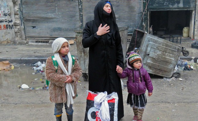 A Syrian woman, fleeing violence in the restive Bustan al-Qasr neighbourhood, reacts as she stands with her children in Aleppo's Fardos neighbourhood on December 13, 2016, after regime troops retook the area from rebel fighters (Picture: Getty)