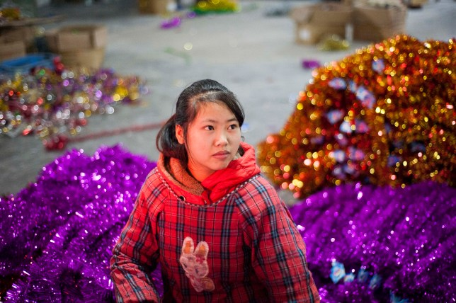 November 28, 2015, Yiwu, China - Zhao Yimin, 15, makes bundles of tinsel by hand at the Xin Shua tinsel factory. She and her mother are migrant workers from Guilin. Zhao attends a middle school for migrant worker, but has worked at the tinsel factory since she was 11 years old. She is paid 0.04 RMB for each bunch of tinsel she tags together by hand and her tally is added to that of her mother. Photo by Dave Tacon / Sinopix