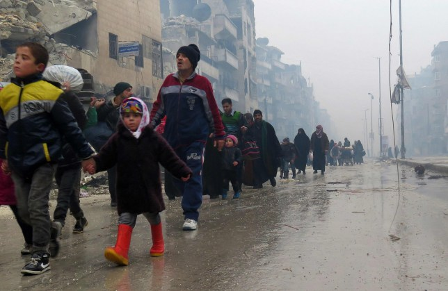 Syrian residents, fleeing violence in the restive Bustan al-Qasr neighbourhood, arrive in Aleppo's Fardos neighbourhood on December 13, 2016, after regime troops retook the area from rebel fighters. Syrian rebels withdrew from six more neighbourhoods in their one-time bastion of east Aleppo in the face of advancing government troops, the Syrian Observatory for Human Rights said. / AFP PHOTO / STRINGERSTRINGER/AFP/Getty Images