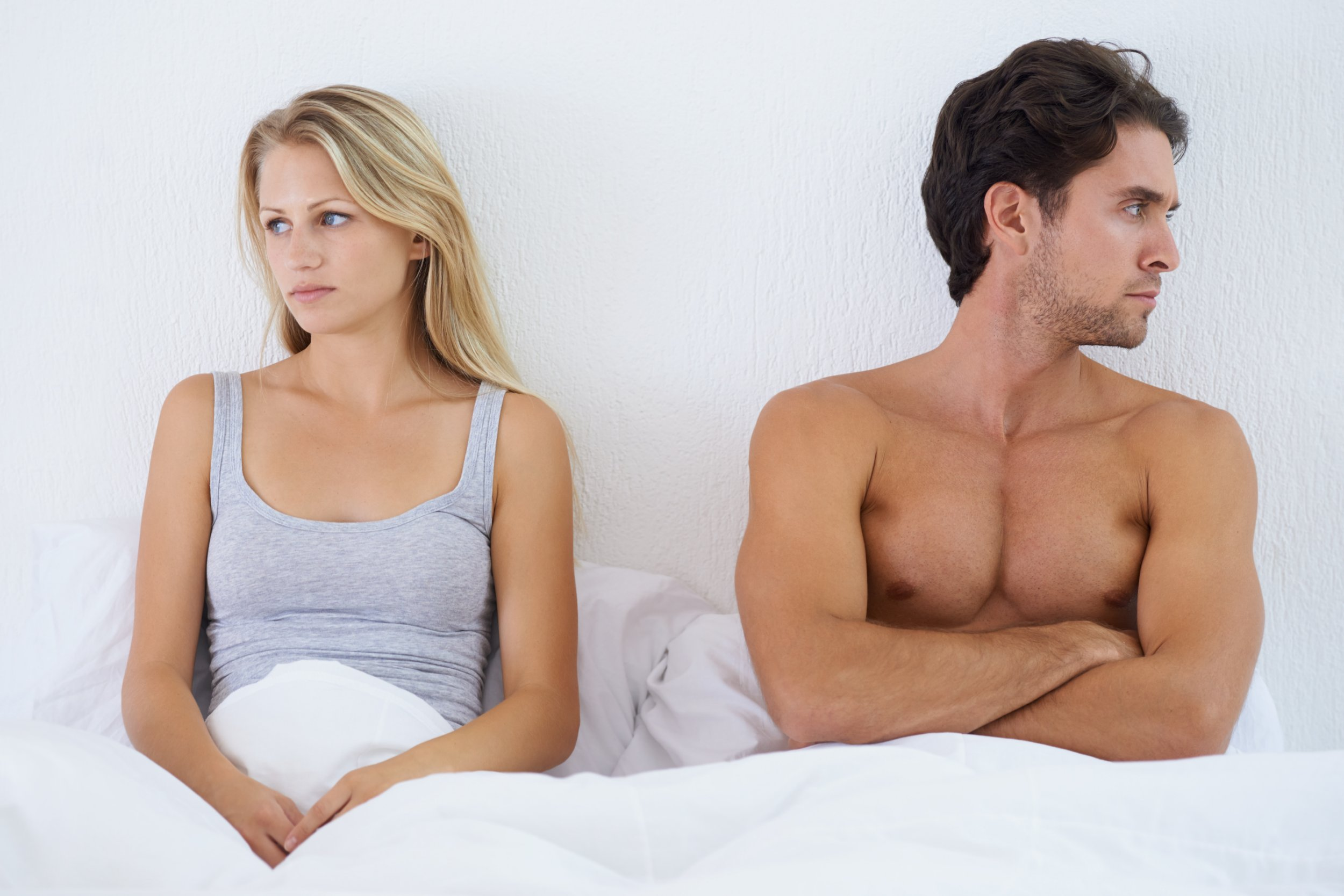 A couple sitting in bed and looking upset after having a disagreement