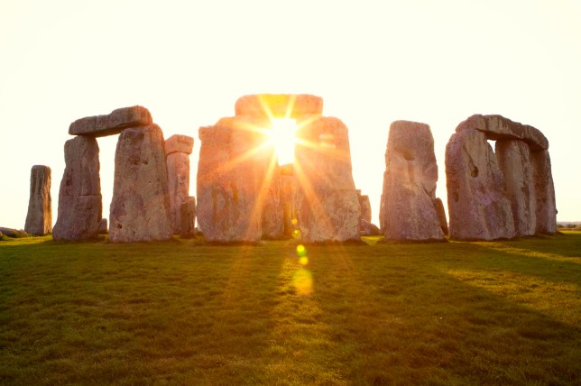 Close-up view of ancient stones during sunset at UNESCO World Heritage Site at Stonehenge, Wiltshire, UK. Sun shines through the stones. Major tourist destination, archeological and pilgrimage site during Summer Solstice and Winter Solstice. Visible grain, softer focus.