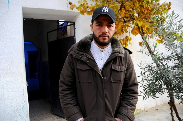 """The brother of fugitive Tunisian extremist suspected in Berlin's deadly Christmas market attack, Abdelkader Amri, poses for a photo in front of the family house where Anis Amri used to live, in Oueslatia, central Tunisia, Thursday, Dec. 22, 2016. Brother Abdelkader Amri told The Associated Press, """"I ask him to turn himself into the police. If it is proved that he is involved, we dissociate ourselves from it."""" (AP Photo/Riadh Dridi)"""